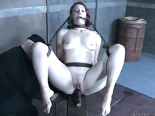 Pale skin redhead lady chained and belted on the wooden post